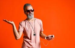 听到与耳机的音乐的一个年长秃头人的图象 库存图片