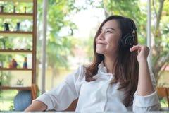 听到与耳机的音乐的一名美丽的亚裔妇女在充满感觉的咖啡馆放松 免版税库存图片