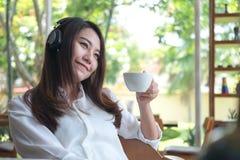 听到与耳机的音乐的一名美丽的亚裔妇女,当喝与感到的咖啡愉快时和在咖啡馆放松 免版税库存照片