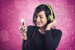 听到与耳机的音乐的友好的微笑的女孩 免版税库存图片