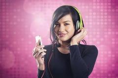 听到与耳机的音乐的可爱的微笑的女孩 免版税库存图片
