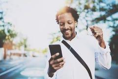 听到与耳机的音乐的可爱的美国非洲黑人在都市背景中 使用智能手机的愉快的人 免版税图库摄影