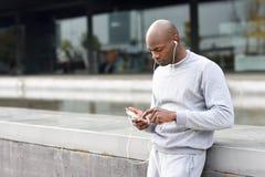 听到与耳机的音乐的可爱的黑人在都市 库存照片