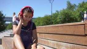 听到与耳机的音乐的女孩坐一条长凳在公园 4K 影视素材