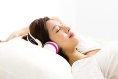 听到与耳机的音乐的妇女在床上 免版税图库摄影