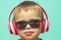 听到与耳机的音乐的孩子 免版税图库摄影