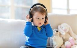 听到与耳机的音乐的小孩男孩 库存图片