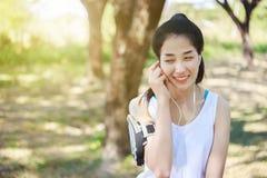 听到与耳机的音乐的少妇在巧妙的电话app 免版税库存照片