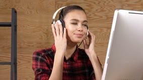 听到与耳机的音乐的年轻美丽的妇女 股票录像