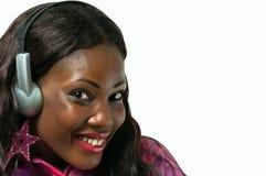 听到与耳机的音乐的微笑的非裔美国人的妇女 库存图片