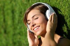 听到与耳机的音乐的愉快的女孩在公园 免版税库存照片