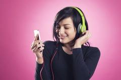听到与耳机的音乐的愉快的女孩 库存照片