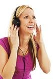 听到与耳机的音乐的愉快的妇女 免版税库存照片
