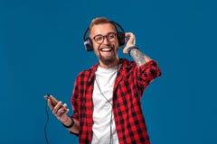 听到与耳机的音乐的愉快的年轻人 方格的衬衣跳舞的英俊的微笑的人与耳机 库存图片