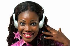 听到与耳机的音乐的愉快的非裔美国人的妇女 免版税库存图片