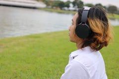 听到与耳机的音乐的愉快的年轻人在自然河放松时间 免版税图库摄影