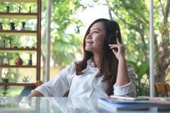 听到与耳机的音乐的美丽的亚裔妇女在充满感觉的咖啡馆放松并且绿化自然 免版税库存照片