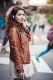 听到与耳机的音乐的美丽的女孩在城市 免版税库存图片