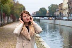 听到与耳机的音乐的美丽的女孩在都市co 图库摄影