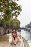 听到与耳机的音乐的美丽的女孩在都市co 库存照片