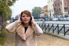 听到与耳机的音乐的美丽的女孩在都市co 免版税图库摄影