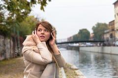 听到与耳机的音乐的美丽的女孩在都市co 免版税库存照片