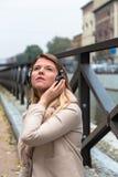 听到与耳机的音乐的美丽的女孩在都市co 免版税库存图片