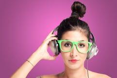 听到与耳机的音乐的美丽的女孩 免版税库存照片