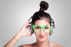 听到与耳机的音乐的美丽的女孩 图库摄影