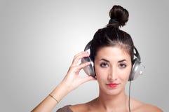 听到与耳机的音乐的美丽的女孩 免版税库存图片