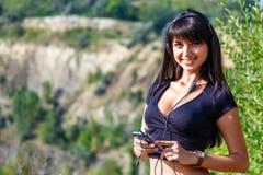 听到与耳机的音乐的美丽的西班牙女孩在a 库存图片