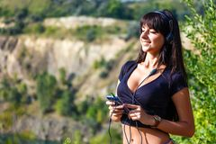 听到与耳机的音乐的美丽的西班牙妇女在s 图库摄影