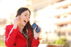听到与耳机的音乐的滑稽的女孩从电话 免版税库存图片
