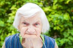 听到与耳机的音乐的年长妇女 库存图片
