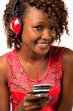 听到与耳机的音乐的年轻非裔美国人的妇女 库存图片