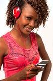听到与耳机的音乐的年轻非裔美国人的妇女 免版税库存图片