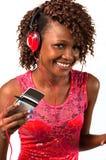听到与耳机的音乐的年轻非裔美国人的妇女 库存照片