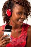 听到与耳机的音乐的年轻非裔美国人的妇女 免版税图库摄影