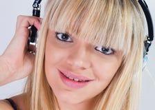 听到与蓝色耳机的音乐的俏丽的女孩 库存照片