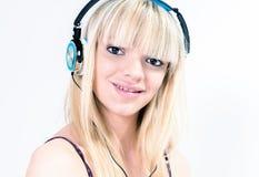 听到与蓝色耳机的音乐的十几岁的女孩 免版税库存图片