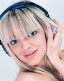 听到与蓝色耳机的音乐的可爱的女孩 免版税图库摄影