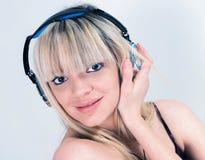 听到与蓝色耳机的音乐的可爱的女孩 免版税库存照片