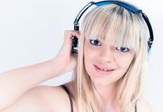 听到与蓝色耳机的音乐的快乐的女孩 免版税库存图片