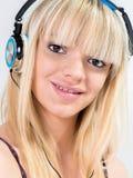听到与蓝色耳机的音乐的白肤金发的十几岁的女孩 免版税图库摄影