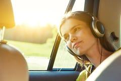 听到与移动的耳机的音乐的微笑的俏丽的女孩  免版税库存照片