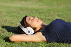 听到与说谎在草的耳机的音乐的轻松的妇女 免版税库存照片