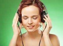 听到与headhones的音乐的年轻愉快的妇女 图库摄影