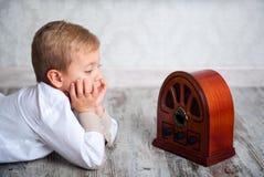 听到减速火箭的收音机的男孩 免版税库存照片