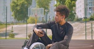 听到在他的坐与a的电话的音乐的年轻坚强的非裔美国人的男性篮球运动员特写镜头画象  股票录像