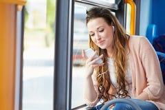 听到在公共汽车的音乐的少妇佩带的耳机 免版税库存照片